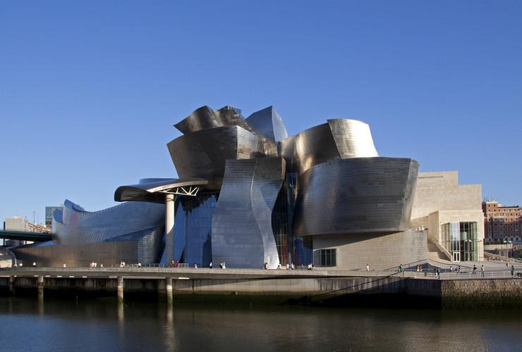 """Gugenhajm, muzej moderne umetnosti u Španiji - Smešten pored reke Nervion, u gradu Bilbao, sagrađen je u industrijskom delu grada. U kategoriji je najboljih građevina 20. veka. Arhitekta Frank Geri težio je """"zdanju sa jakim identitetom"""", kako je sam naveo. Stalna postavka muzeja sastoji se od raznovrsnih elektronskih formi. U kompleksu muzeja postoji i restoran u kome se služe baskijska nacionalna jela."""